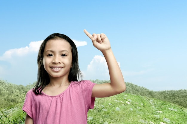 Menina asiática levantando as mãos com um céu azul