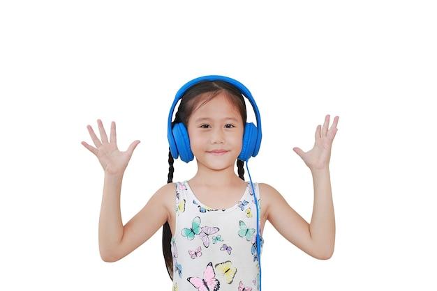 Menina asiática linda com fones de ouvido azuis e mãos abertas, isoladas no fundo branco