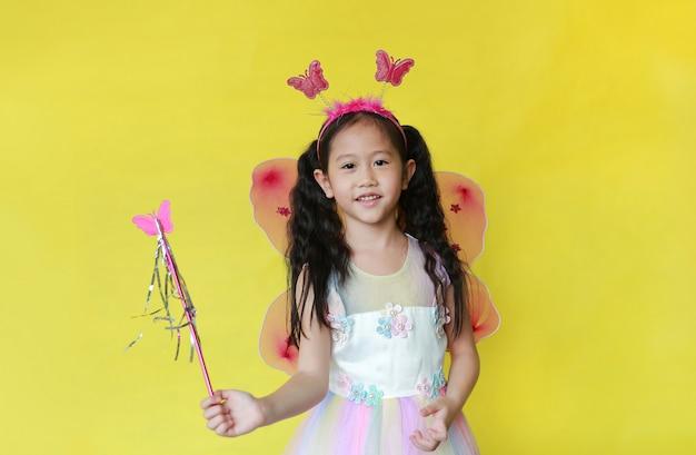 Menina asiática linda criança vestida com fantasia de fada em fundo amarelo