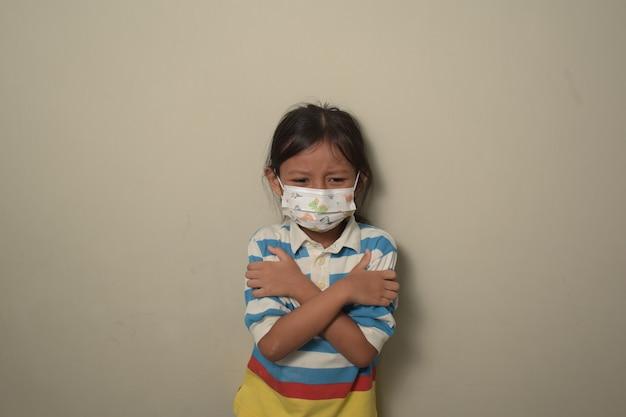 Menina asiática linda jovem usando máscara médica com as mãos no peito devido à febre.