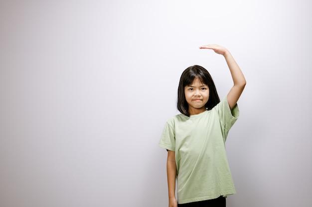 Menina asiática medindo altura perto de uma parede branca