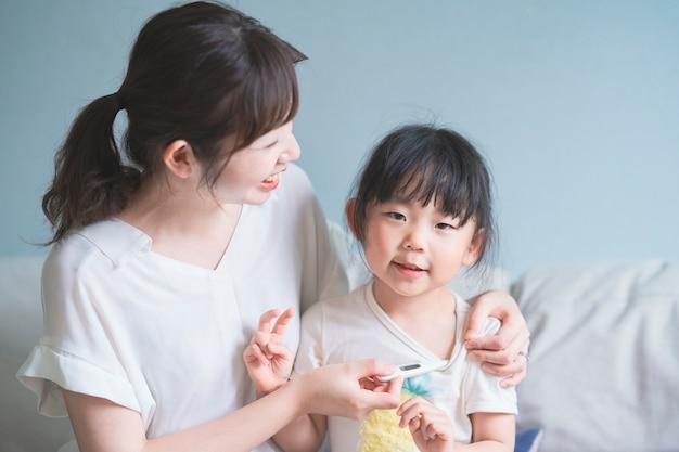 Menina asiática, medir a temperatura do corpo