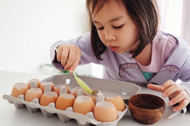 Menina asiática mista plantando sementes em cascas de ovos
