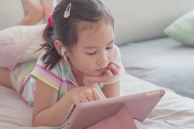 Menina asiática mista usando tablet digital em casa, ouvindo podcast, jogos, educação on-line, elearning, ensino em casa, distanciamento social, isolamento, conceito de bloqueio