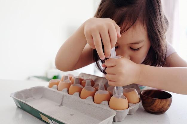 Menina asiática misturada que planta sementes nas cascas de ovo, jardinagem do eco