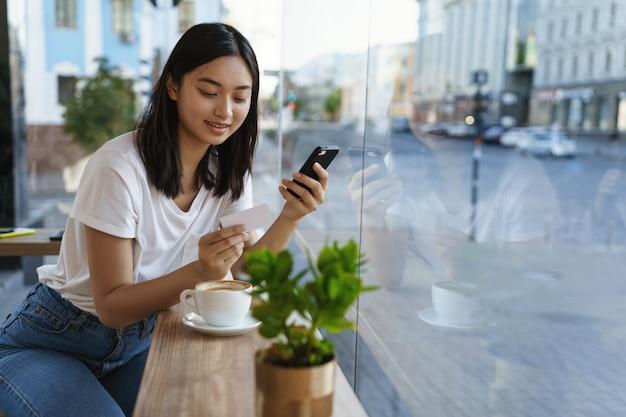 Menina asiática moderna em um café, bebe café, insere o número do cartão de crédito no smartphone.