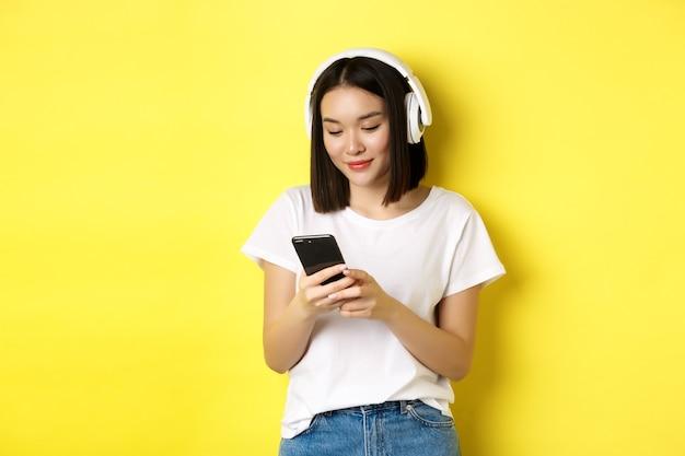 Menina asiática moderna ouvindo música em fones de ouvido sem fio, lendo a tela do smartphone e sorrindo, em pé na camiseta branca sobre fundo amarelo.