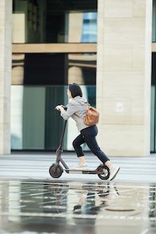 Menina asiática, montando, rapidamente, scooter elétrico