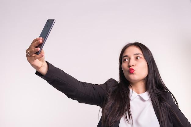 Menina asiática morena com lábios vermelhos fazendo selfie em estúdio
