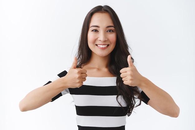 Menina asiática morena confiante, motivada e solidária em uma camiseta listrada, mostrando um gesto de polegar para cima para encorajar alguém que eles fazem melhor, concordar ou aprovar algo, como uma ideia, fundo branco
