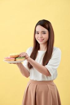 Menina asiática mostra e segurando o prato cheio de saborosos donuts aromáticos deliciosos no rosto de sorriso isolado.