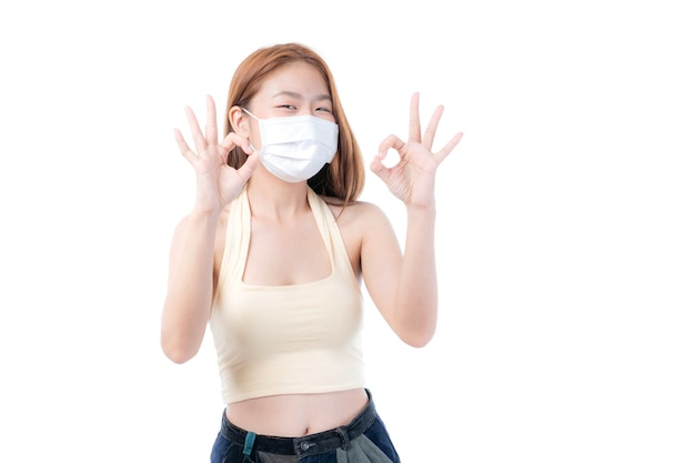 Menina asiática mostra sinal de ok com as mãos usando máscara protetora para proteção durante a quarentena. surto de coronavirus covid19 em fundo branco, proteger propagação covid-19