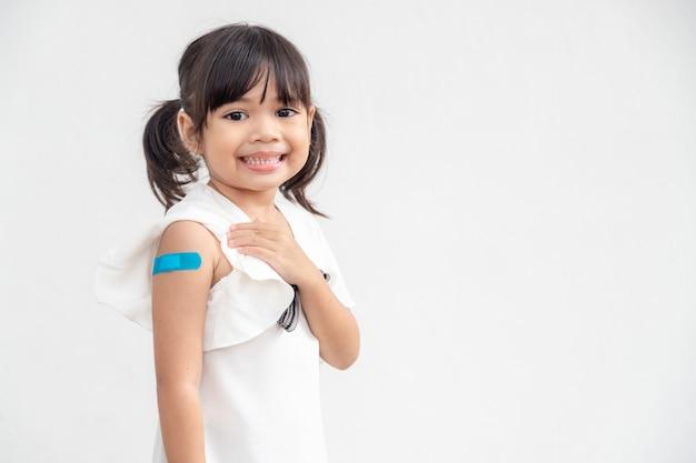 Menina asiática mostrando o braço após ser vacinada ou vacinada com imunização infantil