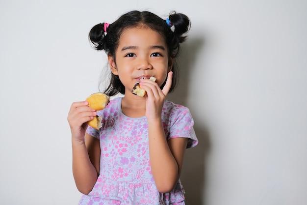 Menina asiática mostrando uma expressão feliz enquanto come um donut