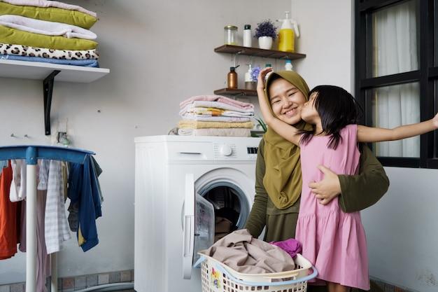 Menina asiática muçulmana com mãe e filha ajudante na lavanderia perto da máquina de lavar