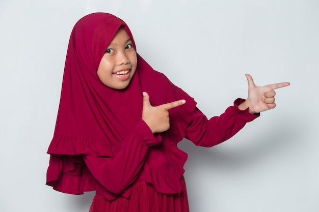 Menina asiática muçulmana hijab apontando para diferentes direções com os dedos