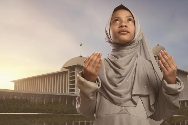 Menina asiática muito asiática no véu rezando a deus