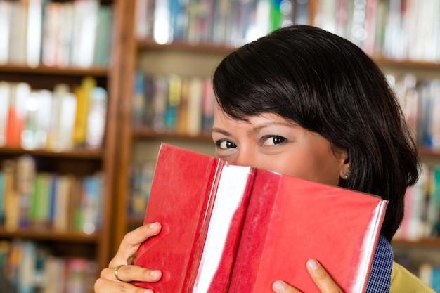Menina asiática na biblioteca, lendo um livro