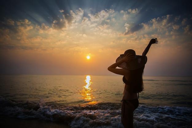 Menina asiática na praia, ela está assistindo o pôr do sol.