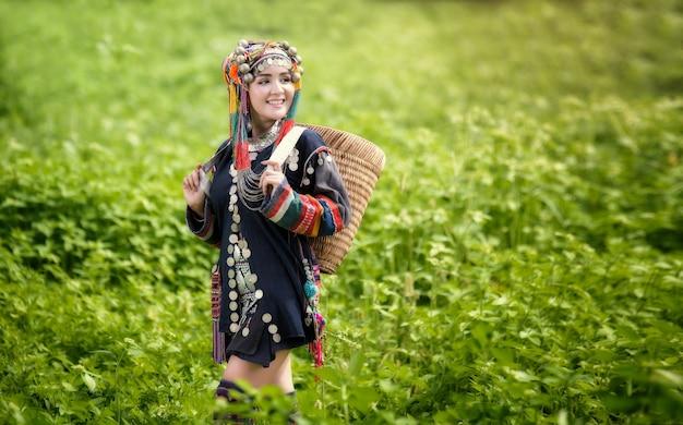 Menina asiática na suíte hmong em campos verdes