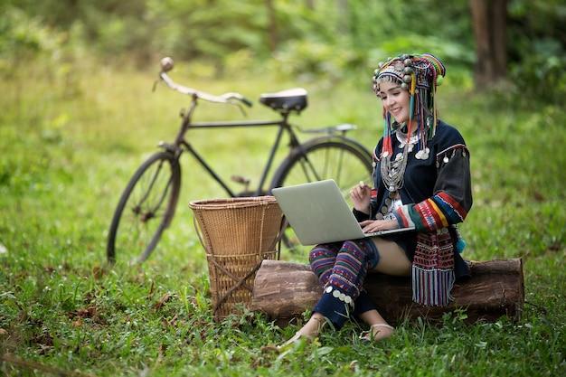 Menina asiática na suíte hmong sentada, jogando laptop na floresta