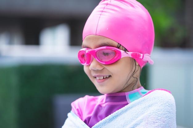 Menina asiática nadando com óculos e toalha