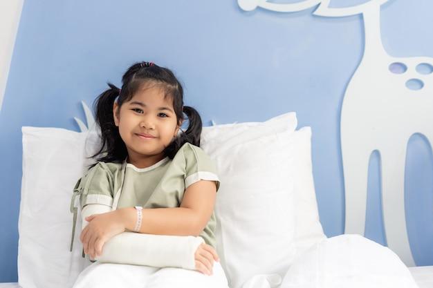 Menina asiática no hospital deitado na cama com um braço quebrado para trás da cirurgia