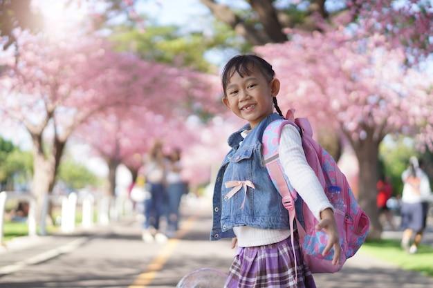 Menina asiática no jardim sob a flor da árvore de sakura