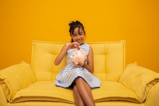 Menina asiática no sofá com um banco de moeda de porco rosa