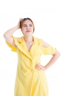 Menina asiática no vestido amarelo mostrando expressões faciais para desconsiderar certas coisas no whiteground branco