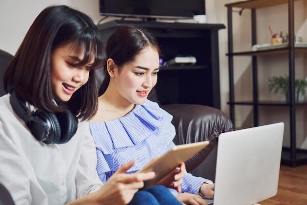 Menina asiática no vestido ocasional azul que escuta a música dos fones de ouvido pretos e o uso do portátil.
