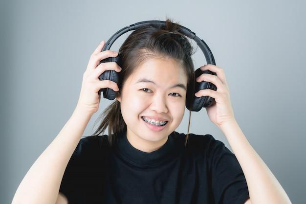 Menina asiática no vestido ocasional preto que escuta a música dos auscultadores pretos.