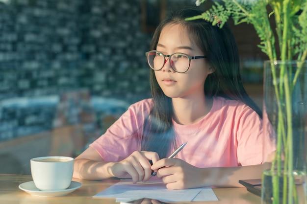 Menina asiática nos vidros que sentam pensamento ocupado ausente durante o trabalho na cafetaria ou no café