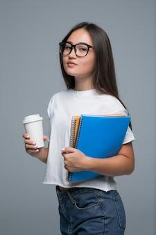 Menina asiática nova com caderno e café para ir nas mãos que estão isoladas contra o fundo cinzento