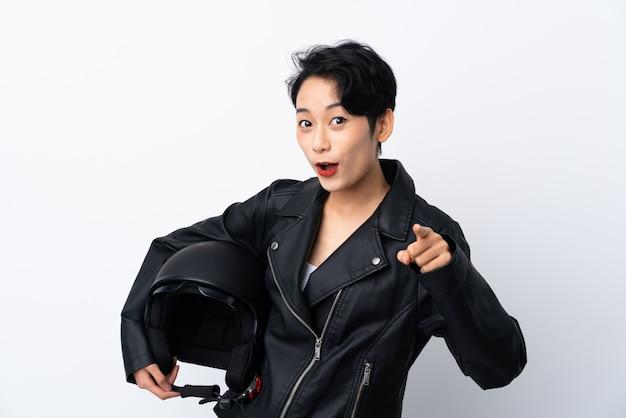 Menina asiática nova com um capacete da motocicleta sobre a parede branca isolada surpreendida e apontando a parte dianteira