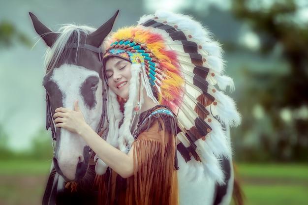 Menina asiática nova da beleza com a mulher do nativo americano e guardar com o cavalo americano da pintura em tailândia.