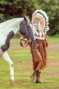 Menina asiática nova da beleza com mulher do nativo americano e passeio com o cavalo americano da pintura em tailândia.