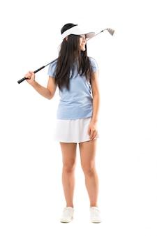 Menina asiática nova do jogador de golfe sobre a parede branca isolada, olhando de lado