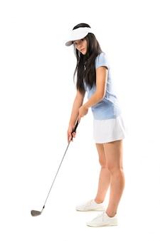 Menina asiática nova do jogador de golfe sobre a parede branca isolada