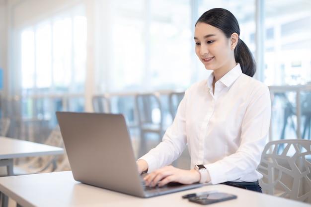 Menina asiática nova do negócio que trabalha com o portátil no café da cafetaria.