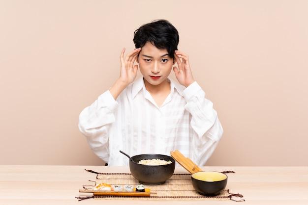 Menina asiática nova em uma tabela com a bacia de macarronetes e sushi infeliz e frustrada com algo. expressão facial negativa