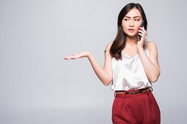 Menina asiática nova no telefone isolado na parede branca
