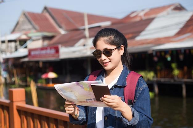 Menina asiática nova que anda no mercado de flutuação de dumonoe saduak, tailândia
