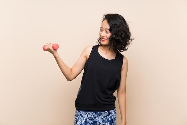 Menina asiática nova que faz o levantamento de peso sobre o fundo isolado com expressão feliz