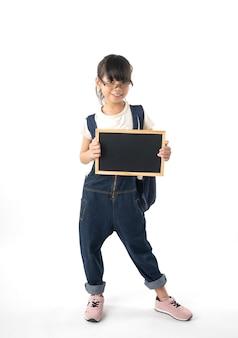 Menina asiática nova que guarda o quadro com o espaço da cópia isolado no fundo branco