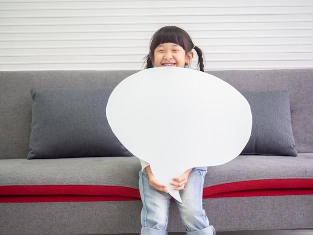 Menina asiática nova que prende um sinal em branco