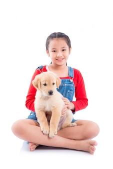 Menina asiática nova que senta-se com seu cão sobre o fundo branco