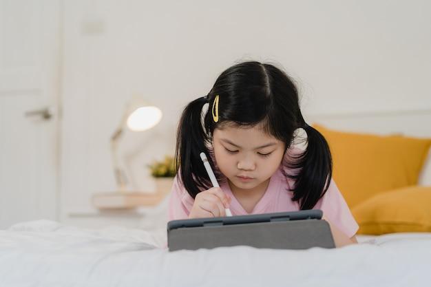 Menina asiática nova que tira em casa. a criança japonesa da criança da mulher de ásia relaxa desenhos animados felizes da tração do divertimento do resto no caderno antes de dormir deitado na cama, sinta o conforto e a calma no quarto no conceito da noite.