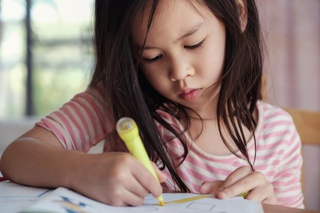 Menina asiática nova que tira em casa, educação homeschool