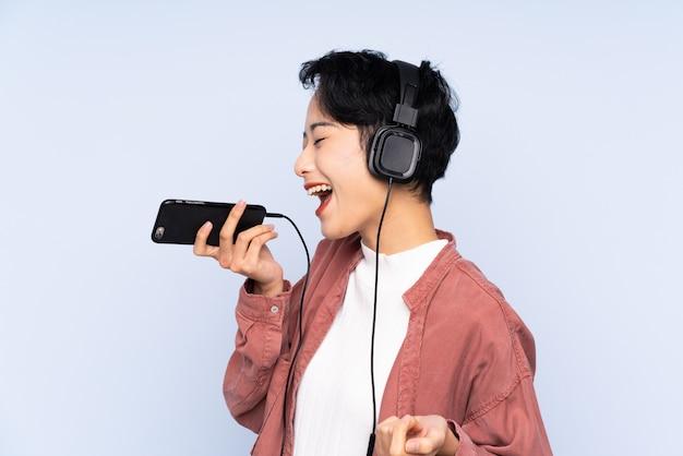Menina asiática nova sobre música de parede isolada azul com um celular e cantando